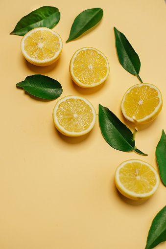 Slices of fresh lemon and lemon leaves on yellow background with copy space