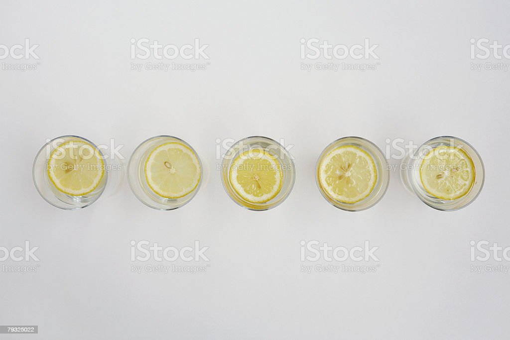Slices of lemon in glasses of water stock photo