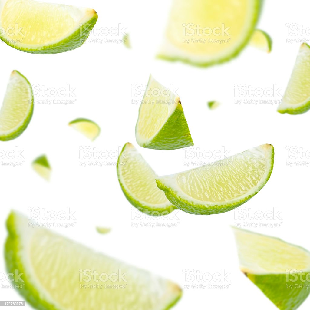 Slices of lime everywhere on white background stock photo