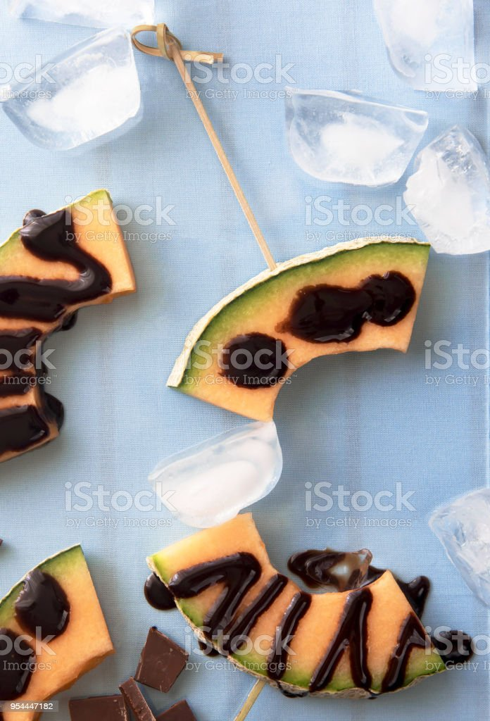 Slices of melon on skewers and watered with dark chocolate. stock photo