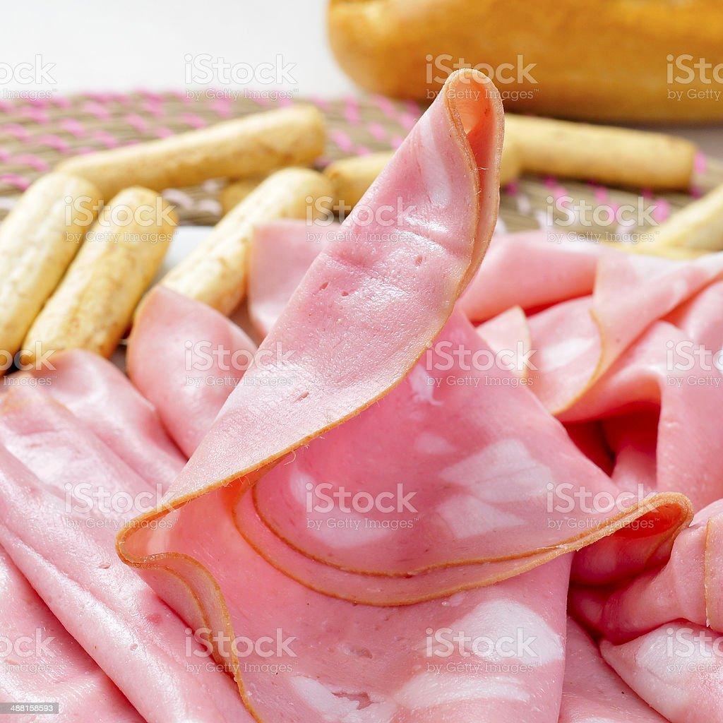 slices of mortadella and bread sticks stock photo