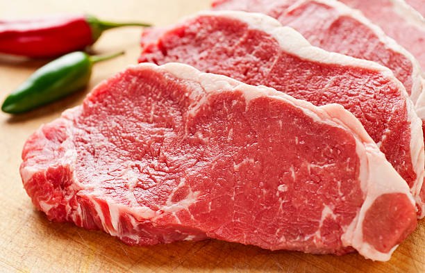 slices of new york strip steak on cutting board - strip steak stockfoto's en -beelden