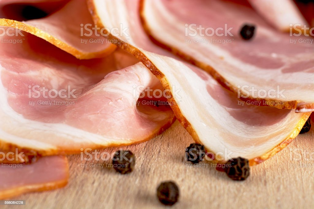Slices of pink bacon with black peppercorn on wooden board stock photo