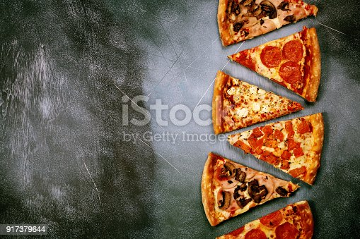 istock Slices of pizza with different fillings on a dark textured background 917379644