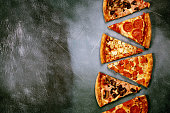 Slices of pizza with different fillings on a dark textured background