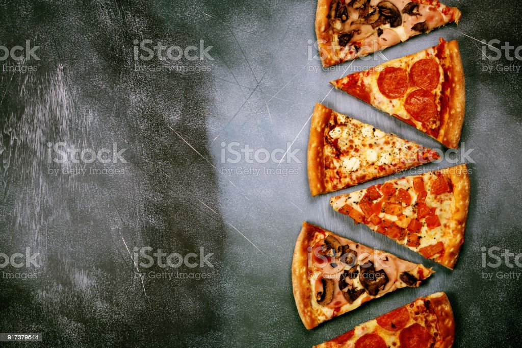 Slices of pizza with different fillings on a dark textured background stock photo