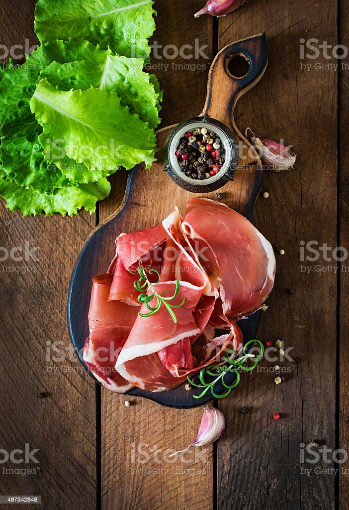 Slices of Prosciutto on old wooden background stock photo