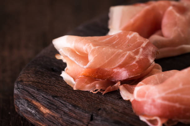 Slices of Prosciutto on old wooden background. stock photo