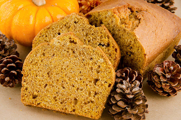 slices of pumpkin bread surrounded by pinecones stock photo