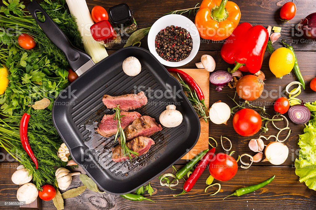 Slices of Rare Beef in Pan with Fresh Ingredients stock photo