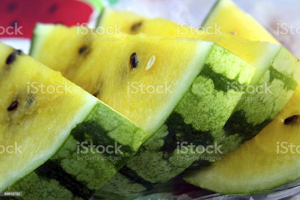Slices of Rare Yellow Watermelon With Black Seeds royalty-free stock photo