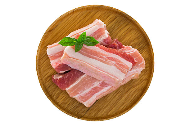 Slices of raw fresh pork belly cut on wooden plate stock photo