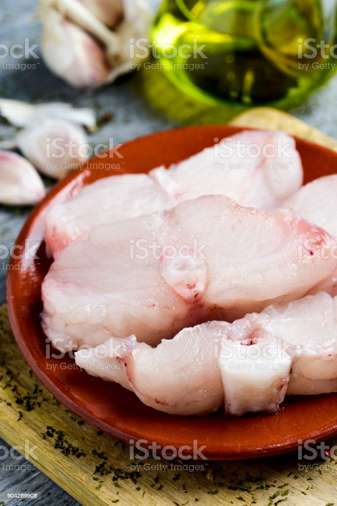 slices of raw monkfish in an earthenware plate stock photo