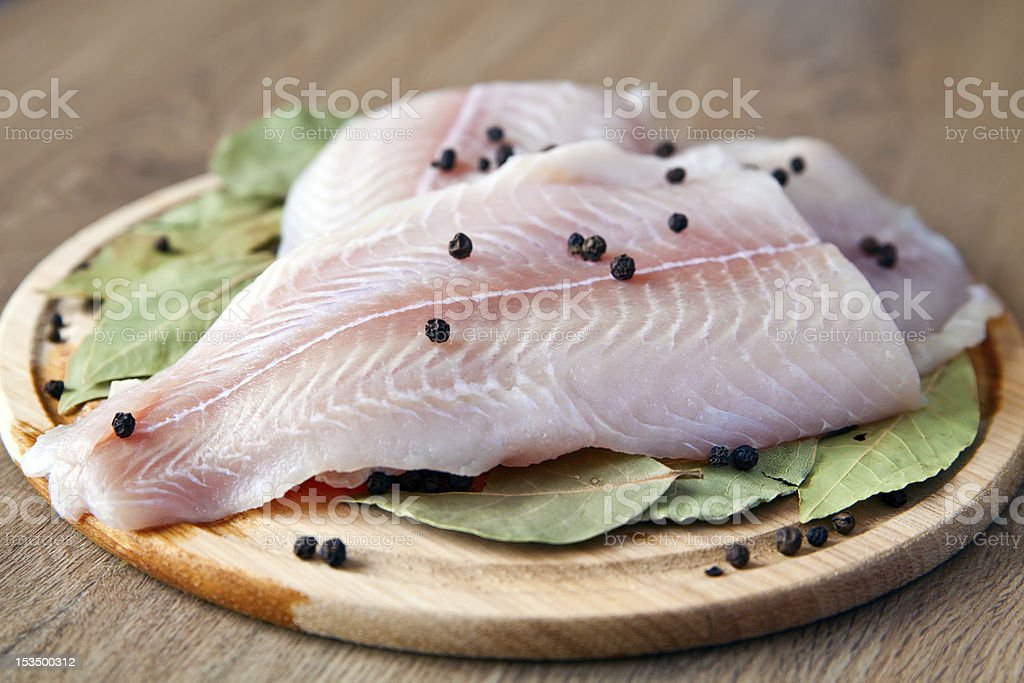 Slices of raw Pangasius with capers and herbs stock photo