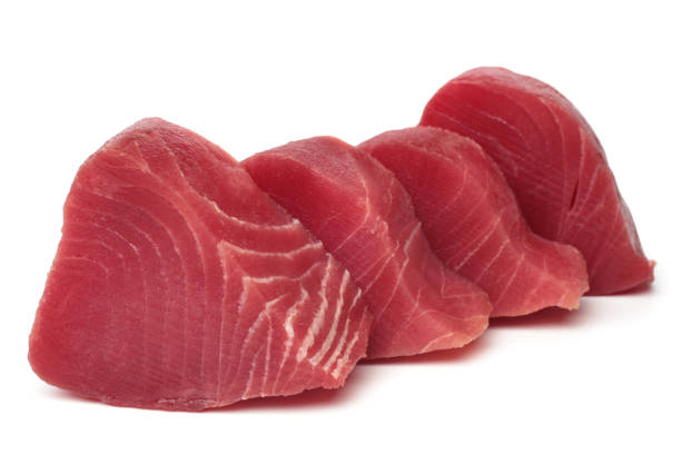 Slices of raw tuna fish meat Slices of raw tuna fish meat on white background tuna seafood stock pictures, royalty-free photos & images
