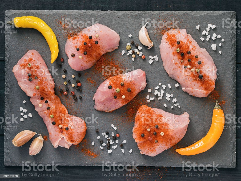 slices of raw turkey meat on slate with seasonings stock photo