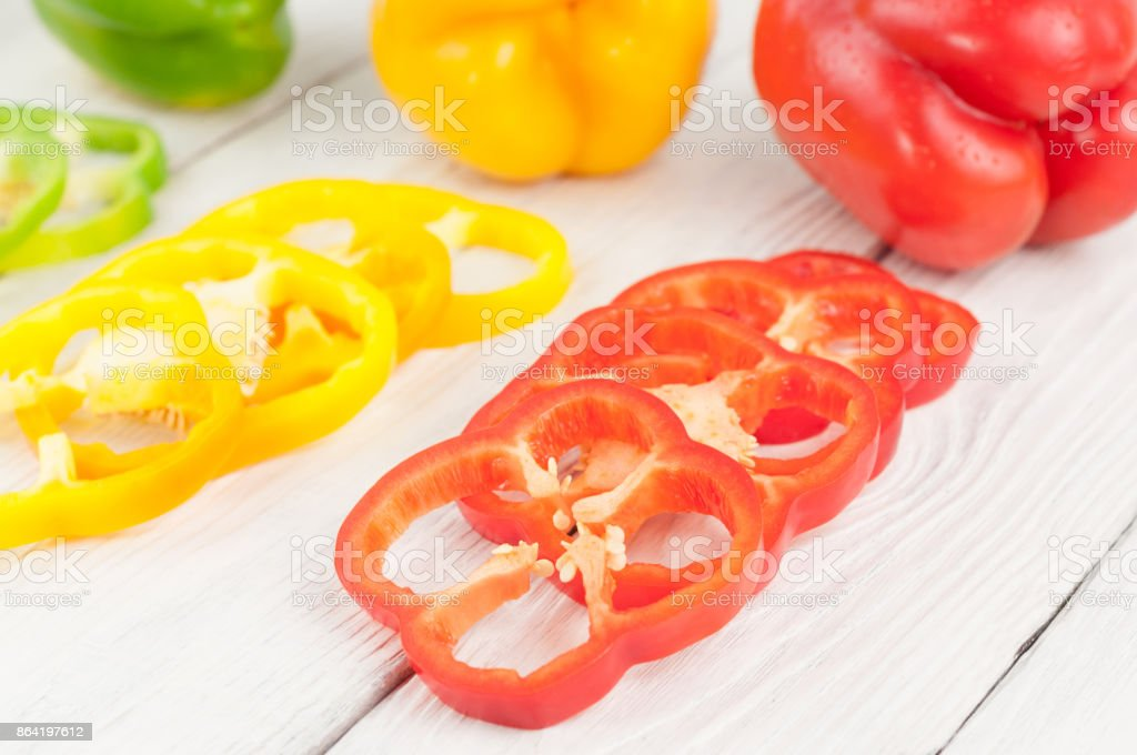Slices of red and green and yellow fresh ripe raw pepper beside colored whole pepper on old rural white wooden planks royalty-free stock photo