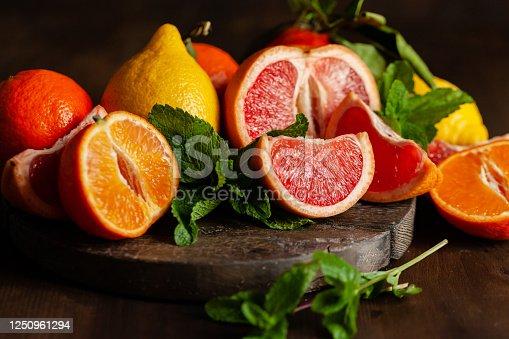 Slices of ripe fresh organic citrus fruits: grapefruit, orange, lemon on wooden board. Natural source of vitamins, low calories tasty dessert. Dark background, close up, front view, macro