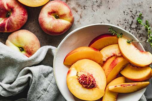 Top view of slices of peach in a bowl. Close-up of ripe peaches slices.
