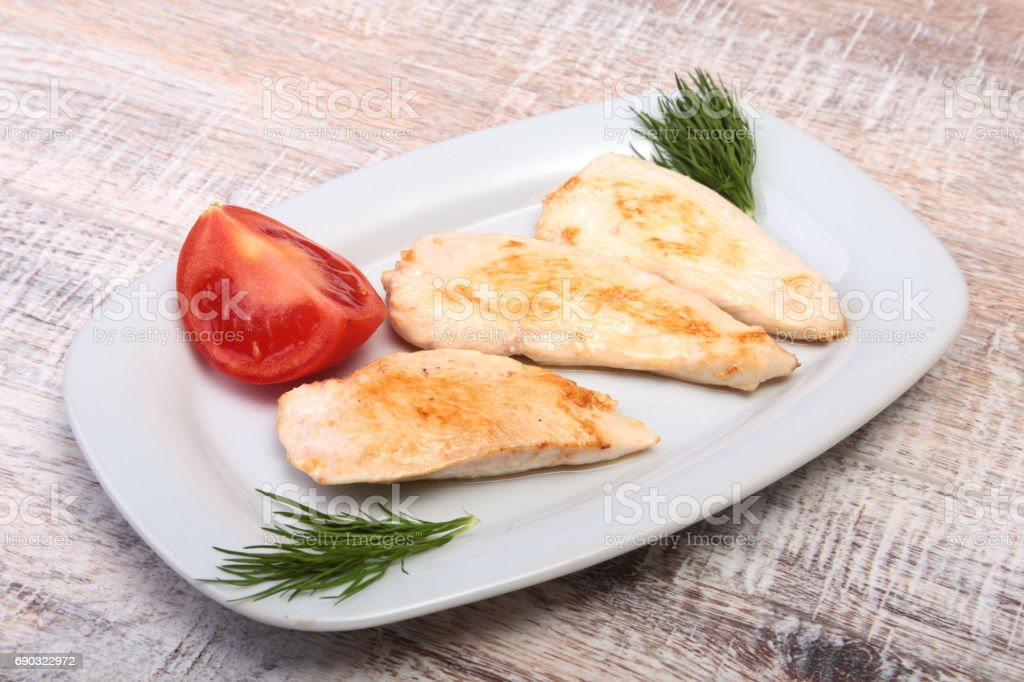 Slices of roasted chicken breast and tomato on white plate stock photo