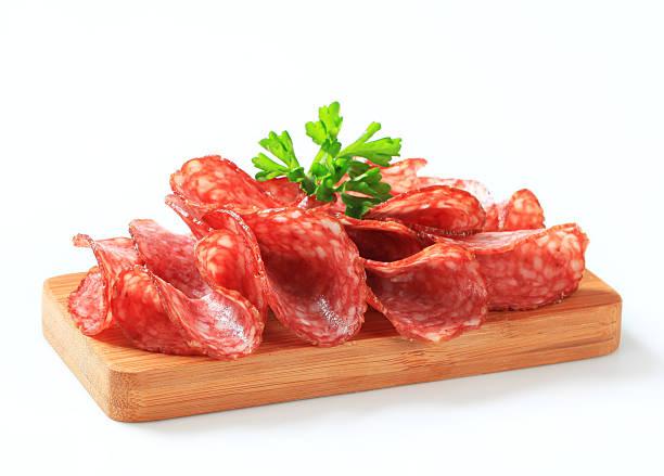 scheiben von salami auf ein schneidebrett - salami vorspeise stock-fotos und bilder