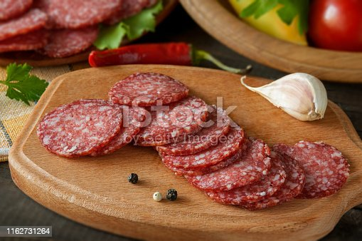 Slices of salami with vegetables pepper and garlic on a cutting board on a wooden table.