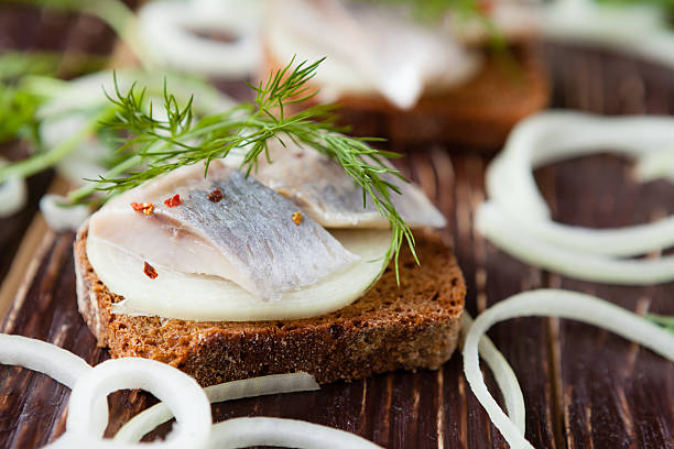 slices of salty herring on whole grain bread with dill stock photo