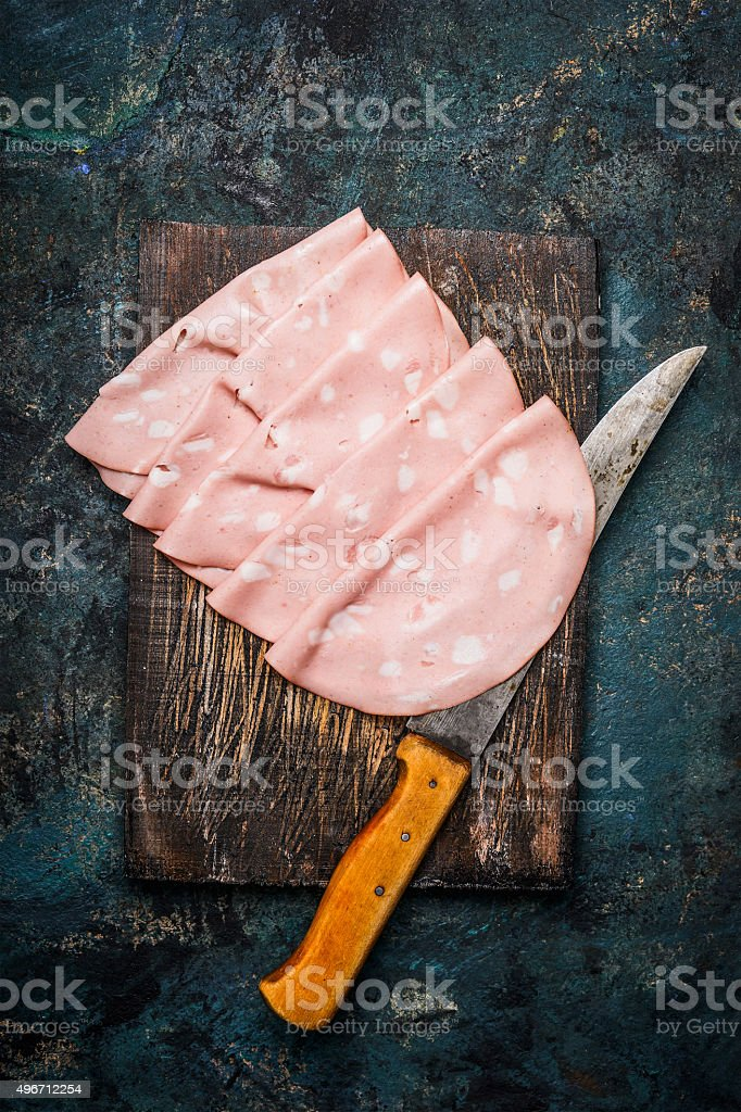 Slices of  Sausage Mortadella di Bologna with kitchen knife stock photo