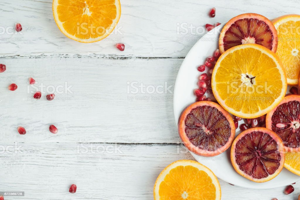 Slices of sicilian orange and common orange on a white wooden table....