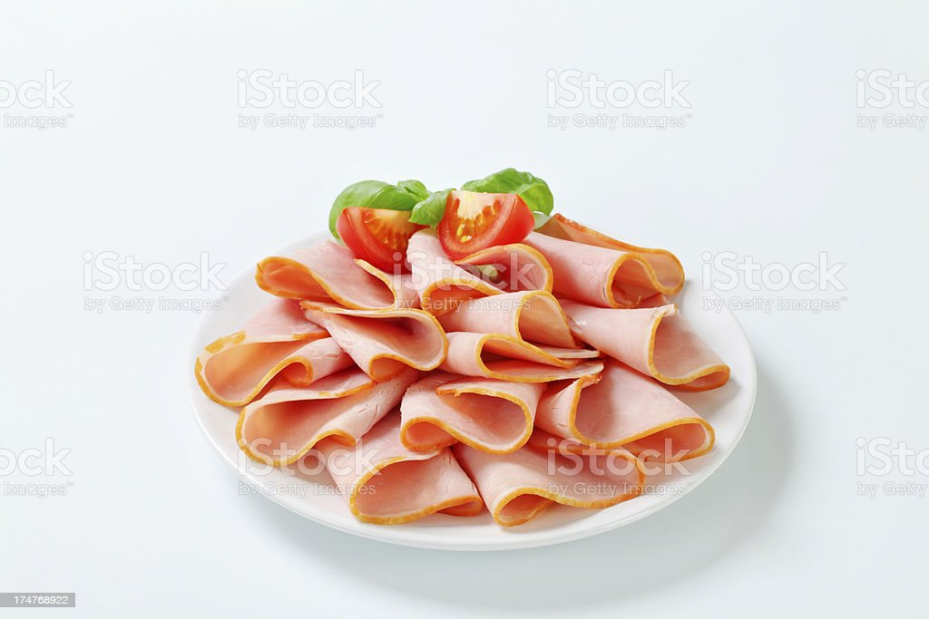 Slices of smoked ham on a plate royalty-free stock photo