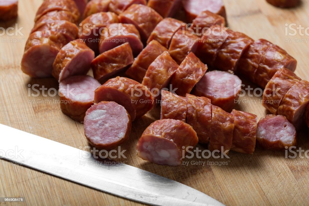 Slices of smoked pork sausage on a wooden cutting board royalty-free stock photo