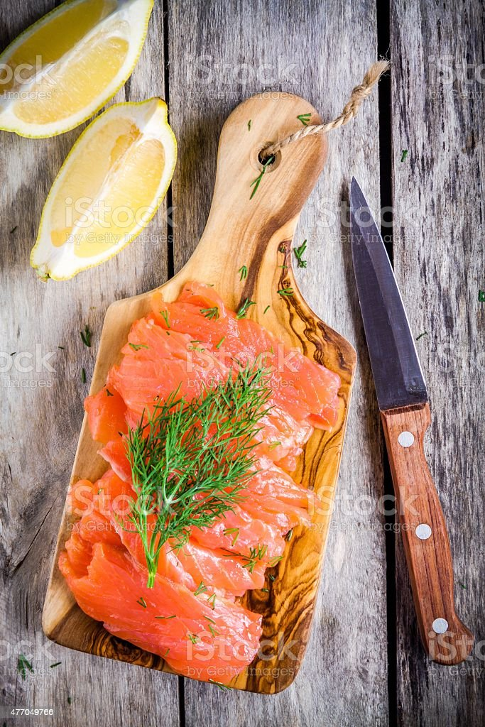 Slices of smoked salmon on a wooden chopping board stock photo