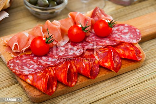 Slices of Spanish dry-cured gammon and two sorts of sausages served on wooden cutting board