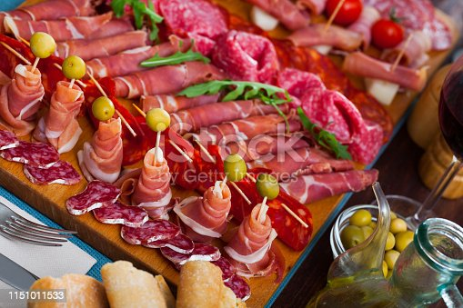 Slices of Spanish dry-cured gammon, variety of sausages and bacon on wooden board garnished with vegetables