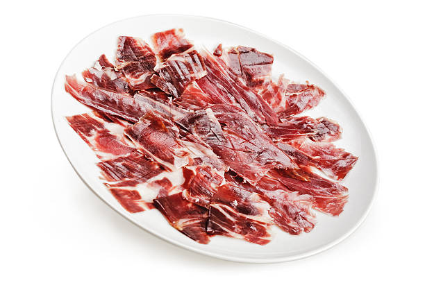 Slices of spanish ham Slices of ham cutted by hand on a white plate over a white background estudio stock pictures, royalty-free photos & images