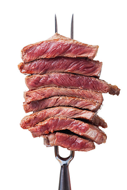 slices of steak slices of steak on a meat fork spit roasted stock pictures, royalty-free photos & images