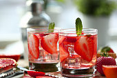 istock Slices of strawberry in a glass of water 1283555447