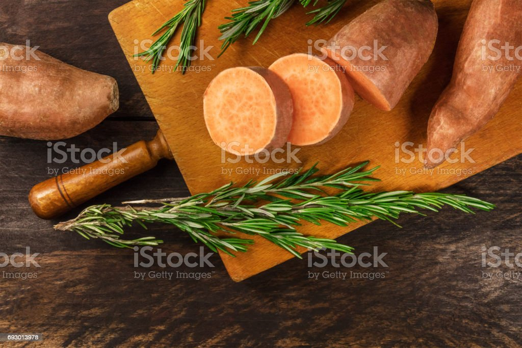 Slices of sweet potatoes with fresh rosemary and copyspace - fotografia de stock