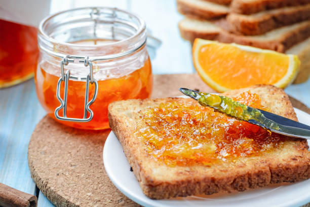 Slices of toasted bread with orange jam for breakfast stock photo