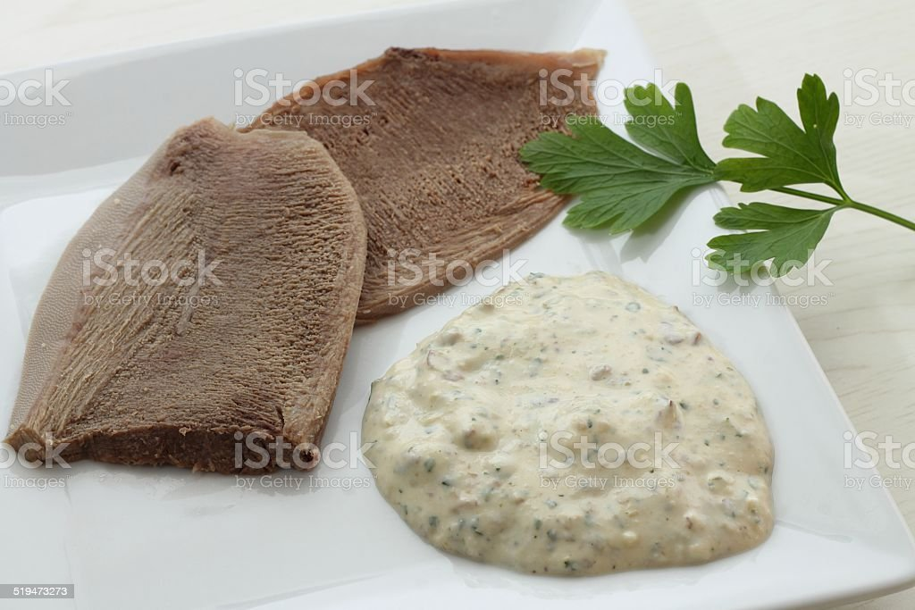 Slices of veal tongue with bagnet verd (parsley sauce) stock photo