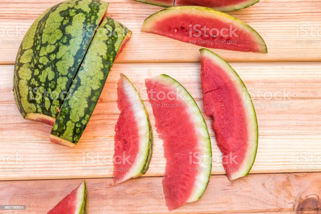slices of watermelon on wooden table, mediterranean garden background - Royalty-free Agriculture Stock Photo