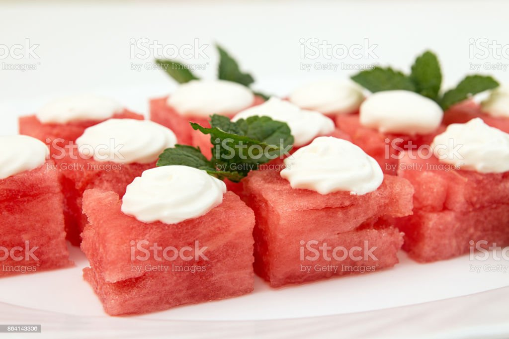 Slices of watermelon with whipped cream scoops on top. sweet summer dessert. Close up. Vegetarian dieting healthy eating. royalty-free stock photo