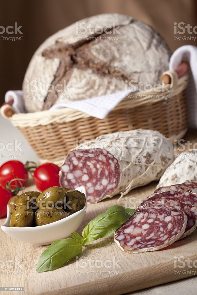 Slices salami on board, cherry tomatoes, olivas, bread, basil royalty-free stock photo