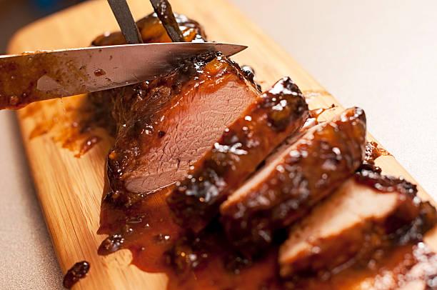 slicing a barbecue pork tenderloin - ossenhaas stockfoto's en -beelden