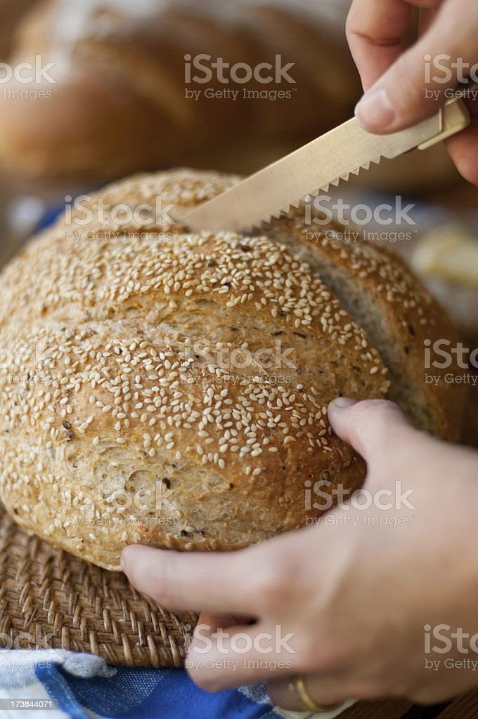 slicing a loaf of bread stock photo