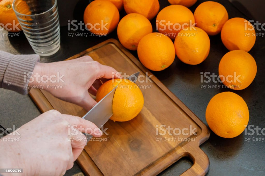 Het snijden van een sinaasappel om verse jus d'orange te maken. Gezonde levensstijl comcept foto