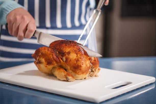 slicing chicken on cutting board - girarrosto foto e immagini stock