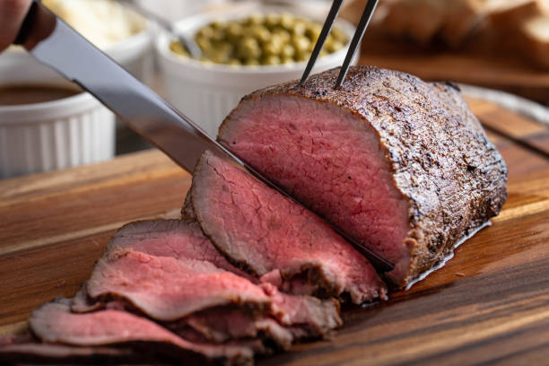slicing eye of round roasted beef with knife slicing eye of round roasted beef with knife roast beef stock pictures, royalty-free photos & images