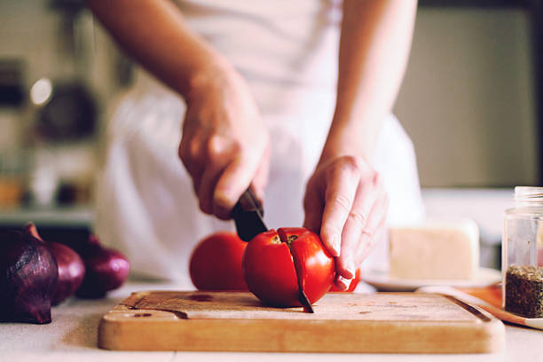 slicing fresh, red tomatoes stock photo