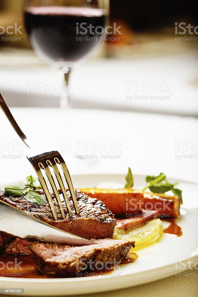 Slicing into juicy steak, red wine on the side royalty-free stock photo